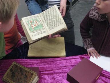 Een oud boek wordt getoond aan kinderen